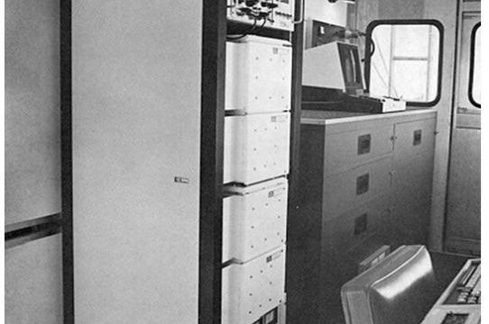 Packet radio equipment in racks; van interior looking backward.