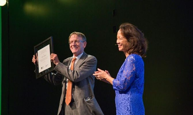 """John Doerr holds high his citation, presented as part of """"Celebrating the Founders and Builders of the Digital Age"""""""