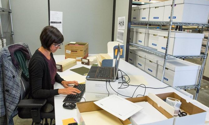 Archivist Kim Hayden works on cataloging the DEC photo library.