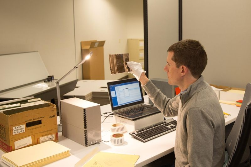 Project Archivist Bo Doub studies a film negative from DEC's Corporate Photo Library before cataloging.