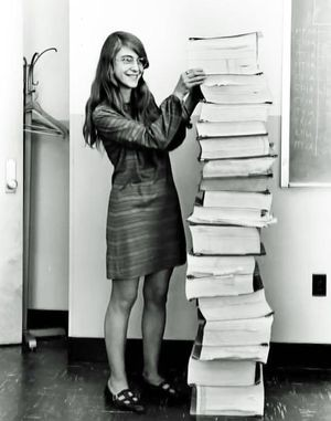 Margaret Hamilton standing with the source code for the Apollo Guidance Computer.