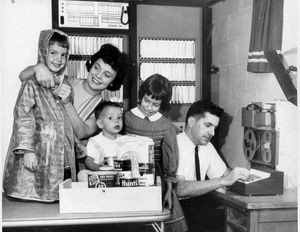 Jim Sutherland sits at the ECHO IV computer. His wife Ruth, puts a raincoat on daughter Sally, while Jay and Ann look on. (Pittsburgh Post-Gazette, 1966)