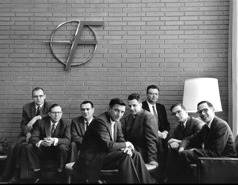 "The ""Traitorous Eight"" pose under the ""Flying F"" logo in the company's Mountain View lobby. From left: Gordon Moore, Sheldon Roberts, Eugene Kleiner, Robert Noyce, Victor Grinich, Julius Blank, Jean Hoerni, and Jay Last. © Wayne Miller/Magnum Photos."