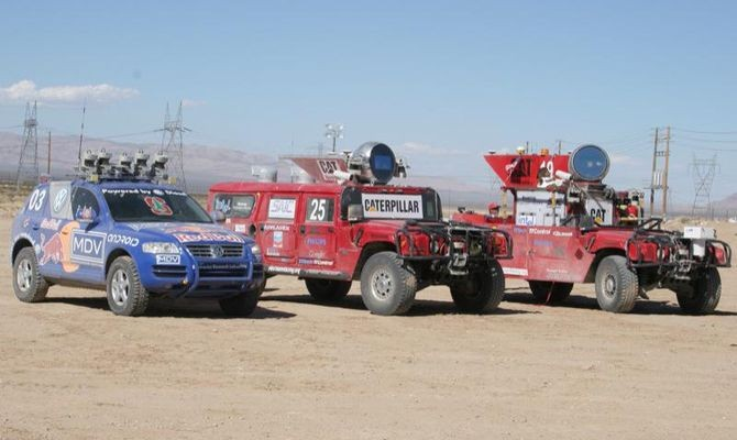 DARPA Grand Challenge winner Stanley (L), runner-ups Sandstorm® and H1ghlander (middle). The winning Stanley VW Touareg team was headed by Stanford Artificial Intelligence Laboratory professor Sebastian Thrun. Carnegie-Mellon's Sandstorm and sister Humvee H1ghlander lagged just behind. All used similar technology, refined from the less successful 2004 event. Credit: Courtesy of Carnegie Mellon University