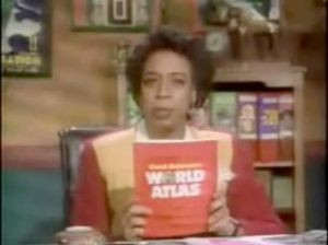 The Chief (Lynne Thigpen) with a World Atlas: one of the prizes from the PBS game show Where in the World is Carmen Sandiego?