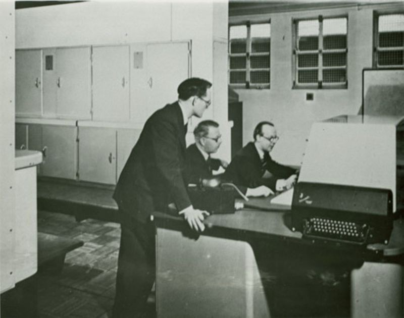Tom Kilburn (standing) at Ferranti Mark I computer, ca. 1950