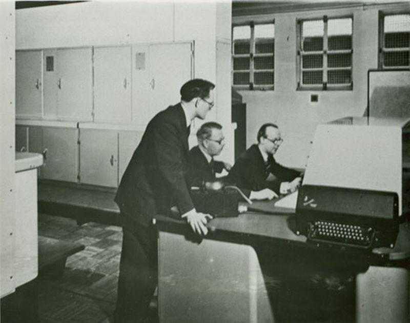 Tom Kilburn (standing) at Ferranti Mark I computer, ca. 1950