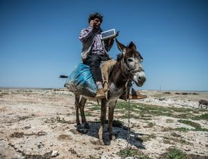 Shepherd with mobile phone and solar-charging panel, Sanliurfa, Turkey, April 25, 2016