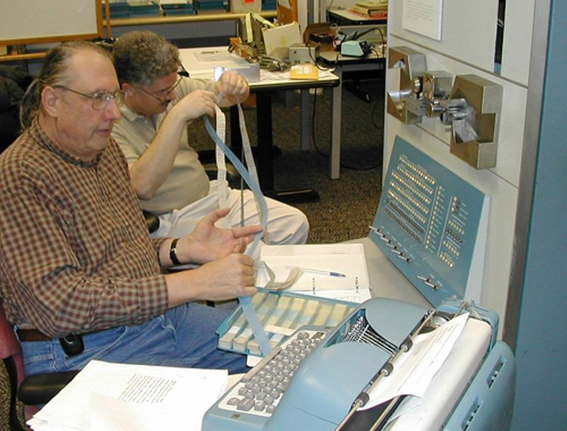 PDP-1 restoration team members, Lyle Bickley and Bob Lash examining paper tapes as part of the PDP-1 restoration project