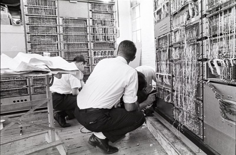 Three men working around PDP-1