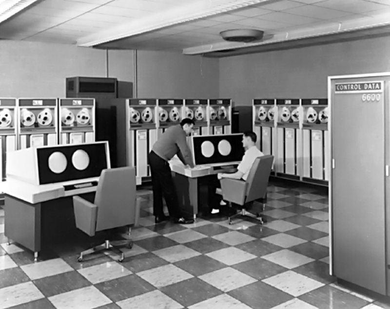 Image shows room containing reel-to-reel tape memory cabinets and two computer input desks with chairs. One operator is standing, talking to the occupant of one of the chairs.